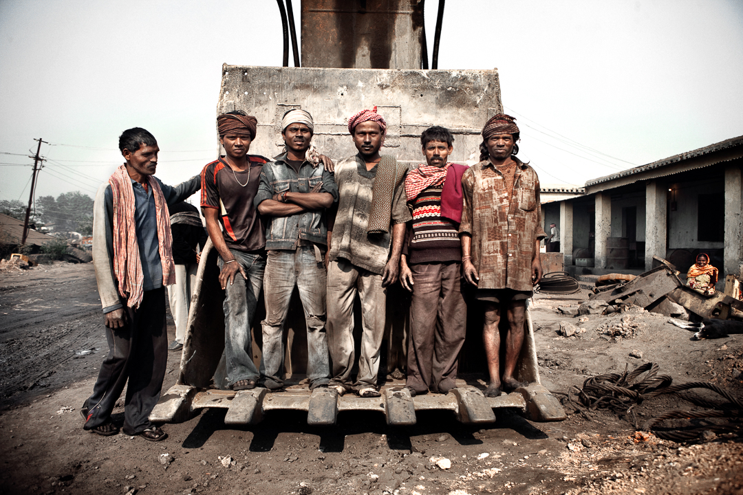 Miners pose for a photo in a mine near Dhanbad  Jharkhand: a mining state of Eastern India – it is the mined coal from here that has made this Indian state world-known for being the second largest coal producer. Second only to China, India extracts from it's soil a quantity of coal overly sufficient for its energy and transport needs; the remainder is exported worldwide.  90% of the mines, which work continuously, are open-air and most of these work upon auto-combustion which releases an incalculable amount of carbon monoxide – the  cause of global warming. Whole forests have been destroyed to make way for this brutal extraction and to satisfy the country's ever-growing development. The concessions for coal mining are granted by the central government and managed by both state and private owned enterprises, thus creating a social and economic imbalance in the area.  Everything rotates around the mining industry which was once an agricultural area and is now fully converted to coal mining.  Many people are jobless and can not cultivate their fields because groundwater aquifers are polluted by agents deriving from coal combustion. These thousands of people, without economic opportunities, are forced to work illegally, in nonexistent safety conditions and with state police always on their backs. The dramatic increase of pollution due to this brutal coal extraction is causing the population to suffer from the most serious respiratory diseases, from lung cancer to silicosis, from many typologies of tuberculosis to obstruction of the respiratory system.  Related, as well, are severe blood diseases caused by carbon monoxide inhalation, cardiac disfunction  and a short-life expectancy (which does not exceed the 50 year mark). These diseases are destroying the future of this Indian state in the name of progress. Throughout the area, new villages are up-starting close to the open-air coal mines, with devastating consequences for the population, who live without the mo
